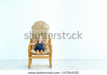 Little baby girl sitting in a rocking chair on the background of a white brick wall.