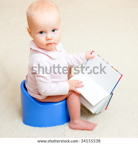 Little baby girl sitting on blue potty with open book - stock photo