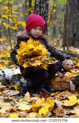 Little baby girl sitting with a bouquet of yellow autumn leaves