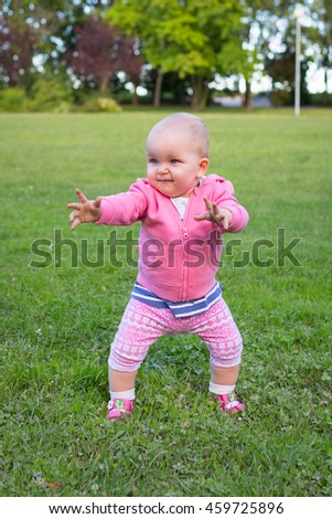 Little baby girl walking in the park - stock photo