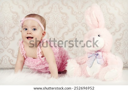 Little baby girl with pink plush rabbit - stock photo