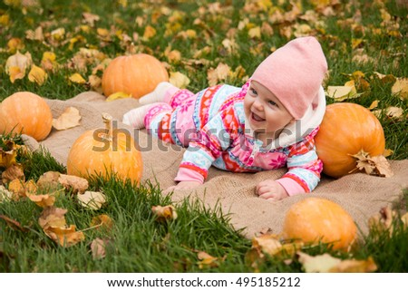 Little baby girl with pumpkins
