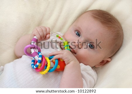 Little baby girl with rattle 2 - stock photo