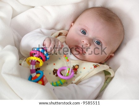 Little baby girl with rattle - stock photo