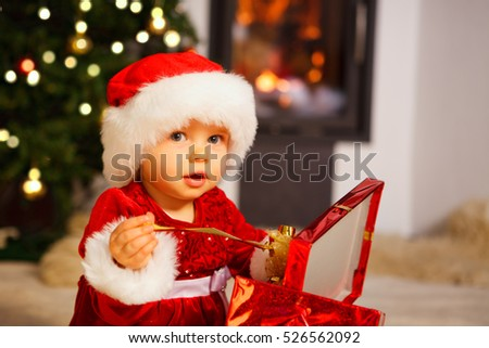 little baby girl with santa hat and present