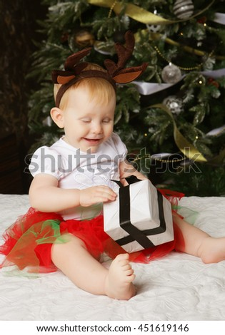 Little baby girl with the gift box near  Decorating Christmas tree. Happy time.  - stock photo