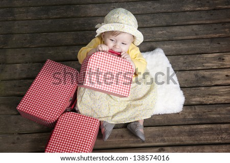 little baby girl with vintage suitcases on an old wooden floor - stock photo