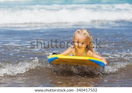 Little baby girl - young surfer with bodyboard has a fun on small sea waves. Active family lifestyle, people outdoor water sport lessons and swimming activity on surf camp summer vacation with child. - stock photo