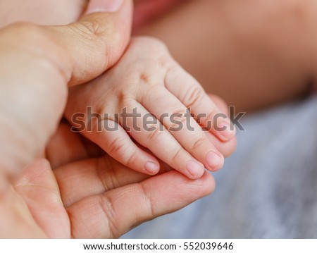 Little baby hand  hold her mother finger