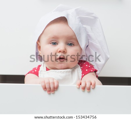 little baby in a chef's hat in the kitchen - stock photo