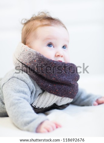 Little baby in a frey knitted sweater and big brown scarf - stock photo