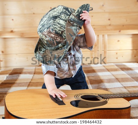 Little baby in cowboy hat playing the guitar - stock photo