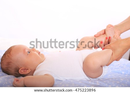 Little baby in diaper lying on bed