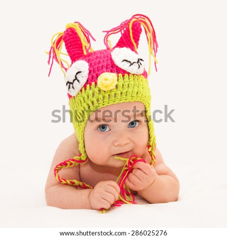 Little baby in funny hat lying on his tummy with his head up on light  sheet background. Selective focus on baby face.  - stock photo