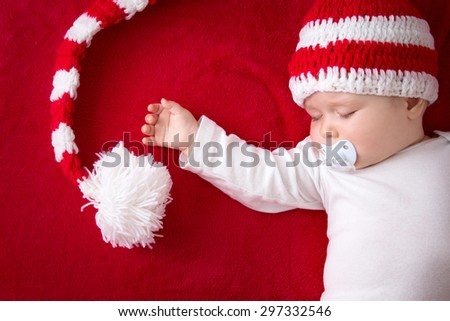 little baby in knitted red whitey hat on red blanket - stock photo