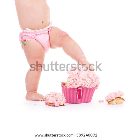 little baby in pink standing on pink birthday cake for first birthday - stock photo