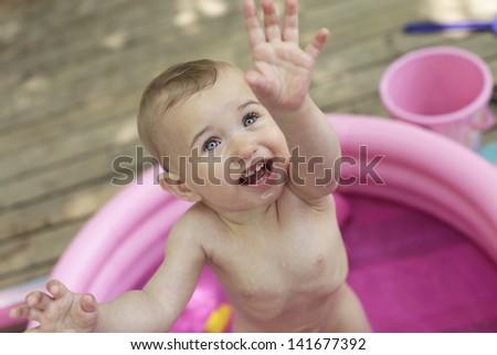 Little baby in plastic pool - stock photo