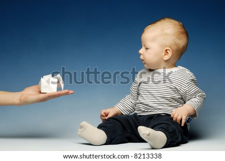 Little baby in sailor's cloths reaching out for a paper boat - stock photo