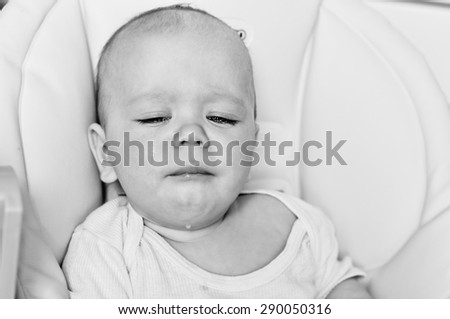 little baby is crying and sitting in the chair - stock photo