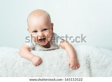 Little baby is smiling on the  white carpet - stock photo