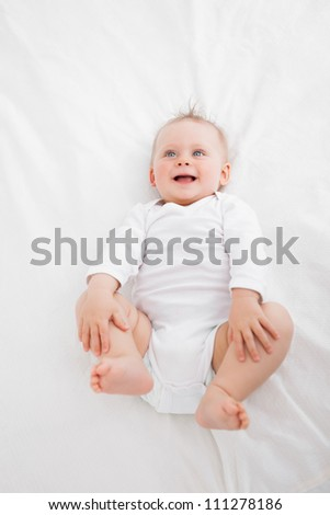 Little baby laughing while lying on a blanket indoors