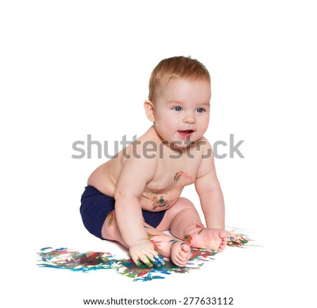 little baby leaning forward and playing with bright colors, getting messy hands and face. On white background - stock photo