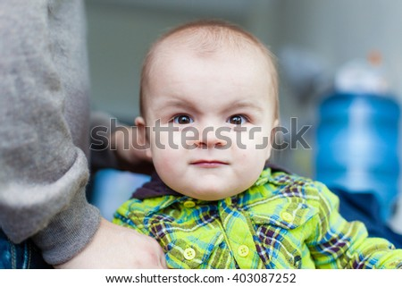 Little baby makes faces at the background of water cooler, closeup, smiling, nice - stock photo