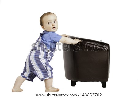 little baby moves a small chair - stock photo