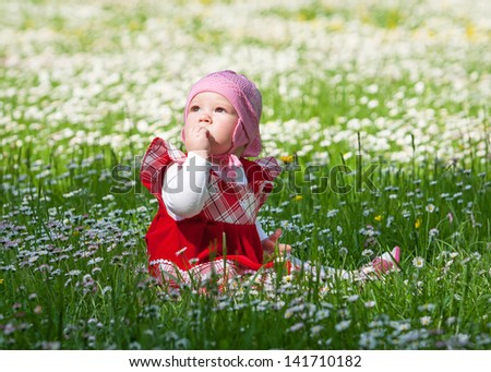 little baby on green grass and flowers