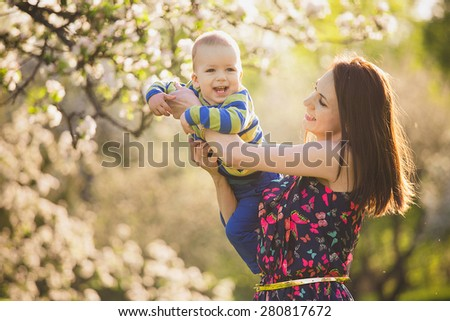 little baby on hands of mother. woman playing with child outside in blooming spring garden. portrait of family of two people. happy family concept. spring landscape background. apple trees in blossoms - stock photo