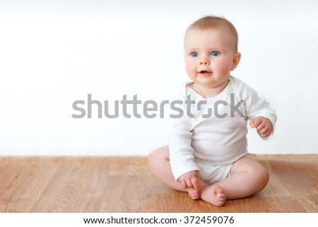 little baby on wooden floor - stock photo