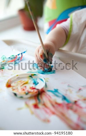 Little baby painting on white paper. Closeup view - stock photo