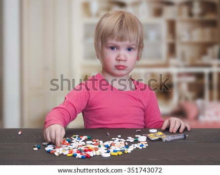 Little baby pills and a syringe. Girl playing with pills. Danger game with medication. The need for parental control of medicines. The room, the child at the table. Blonde hair. - stock photo