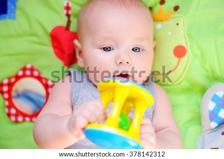 Little baby play with bright toy  - stock photo
