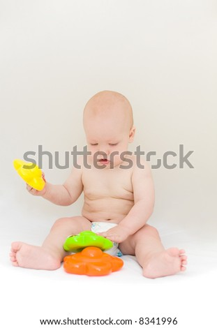 Little baby playing with toys over light gray background - stock photo