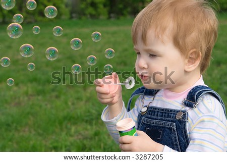 little baby puff up soap bubbles over green