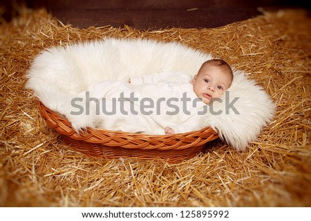 Little baby resting in basket on haystack  straw background