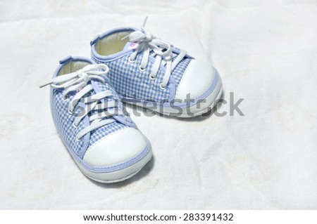 little baby shoes in blue on white fabric.