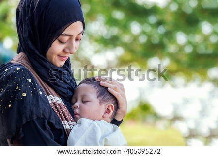 little baby sleeping in hug is muslim mother - stock photo