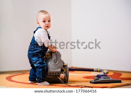 Little baby standing at vacuum cleaner - home interior - stock photo