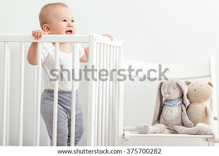 Little baby standing in his crib. - stock photo