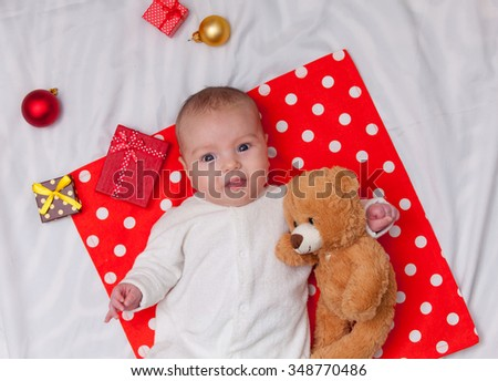 Little baby with christmas gifts and teddy bear on a white background - stock photo