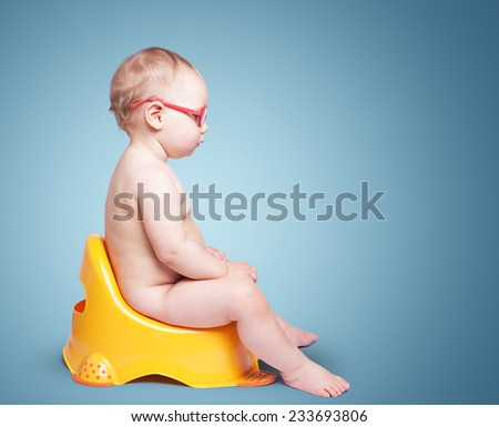 little baby with glasses sitting on the toilet, on color background