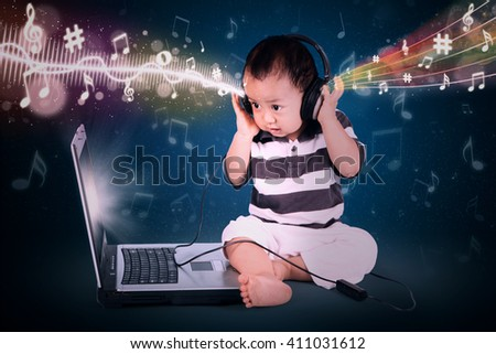 Little baby with headphone listens to a music and looking at laptop screen - stock photo