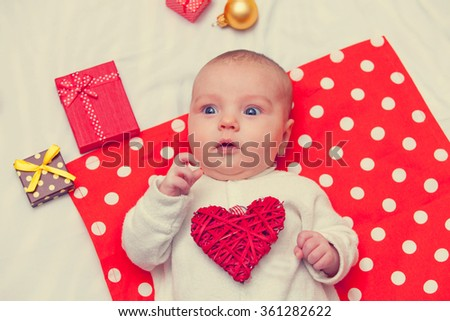 little baby with heart shape toy lying down on red napkin