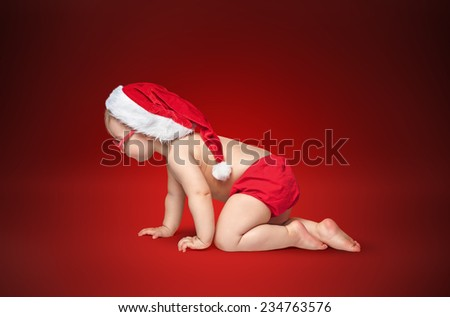 little baby with Santa hat and glasses crawling on rad background. - stock photo