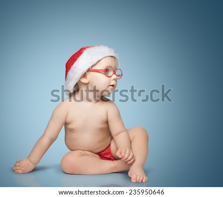 little baby with Santa hat and glasses sit on color background
