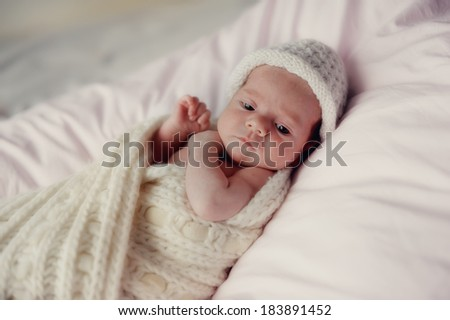 little baby wrapped in a knitted blanket and a white knitted cap
