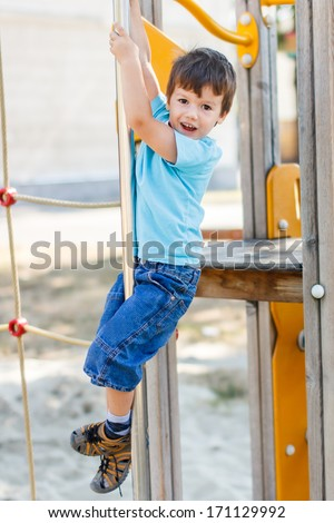 Little bad boy slide down on pole, outdoors - stock photo