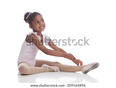 Little Ballerina.  Adorable little girl warming up in her ballet slippers and leotard.  Isolated on white with room for your text.